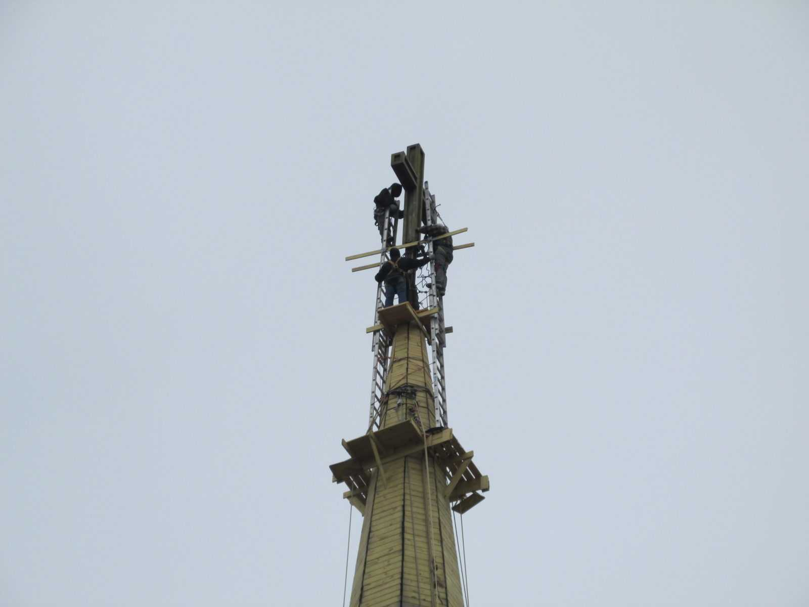 Steeplejacks installing cross